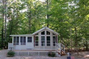 This cottage in the woods is for sale at Lake Forest RV Resort in New Hampshire.